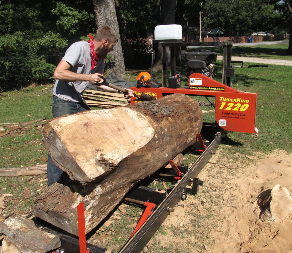 """Jim's son, Jonathan, builds furniture from lumber his dad saws. Here's Jonathan stripping bark off a 27"""" diameter maple."""