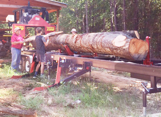 John (left) and his son, Selik, are a sawing team with John's TimberKing 2200 Diesel. Here they remove a freshly-sawn slab.