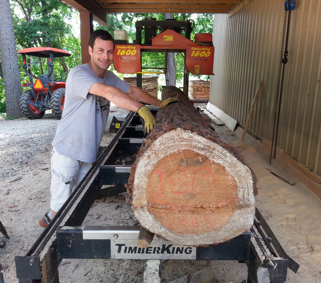 "Here's Tim's eldest son, Andy, getting ready to saw their 100th log into lumber. You can just barely see ""100 Logs"" written on the log's butt end."