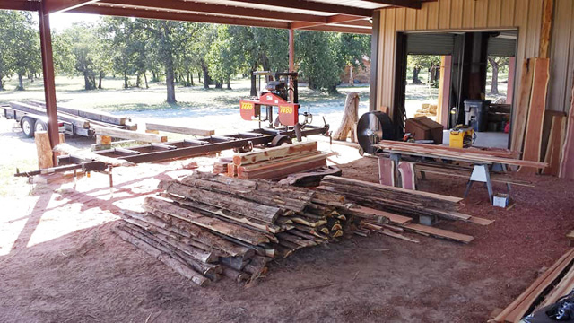 Open for business -- This is what a sawmill business looks like. A yard with a TimberKing mill, some raw materials, and sawn boards ready to go.