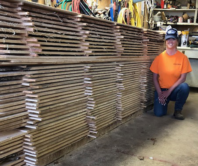Here's Brianna with a stack of boards the couple sawed recently.